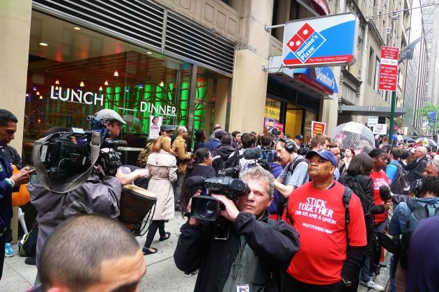 Demonstranterna har samlats utanför en Domino's Pizza strax söder om Times Square.