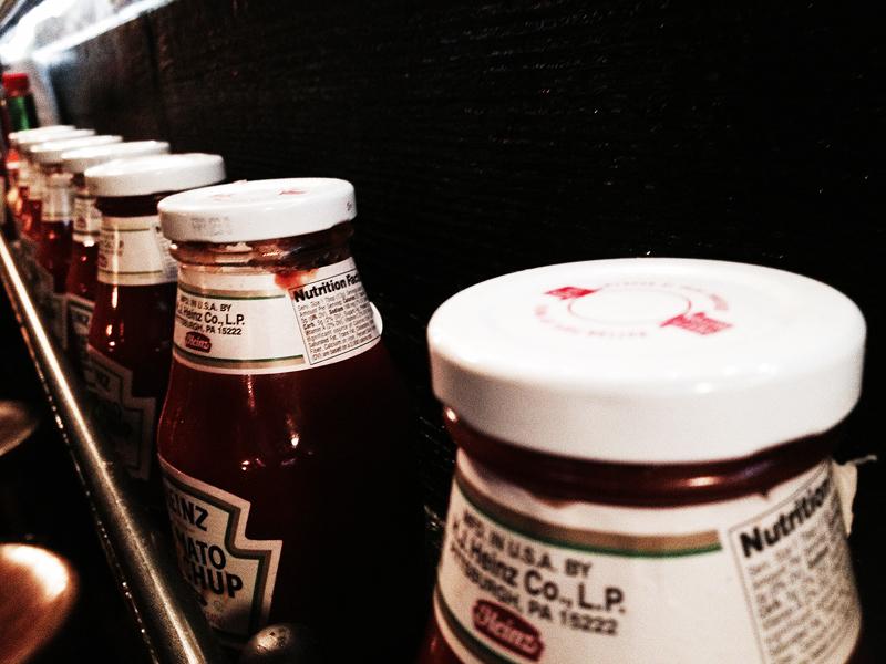 Rader av ketchup klänger längs väggen bredvid de få borden.