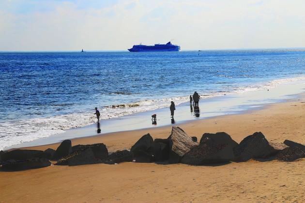 Stranden vid Coney Island. En passagerarfärja, som kanske borde kallas kryssningsfartyg, löper ut från New Yorks hamn vid horisonten.