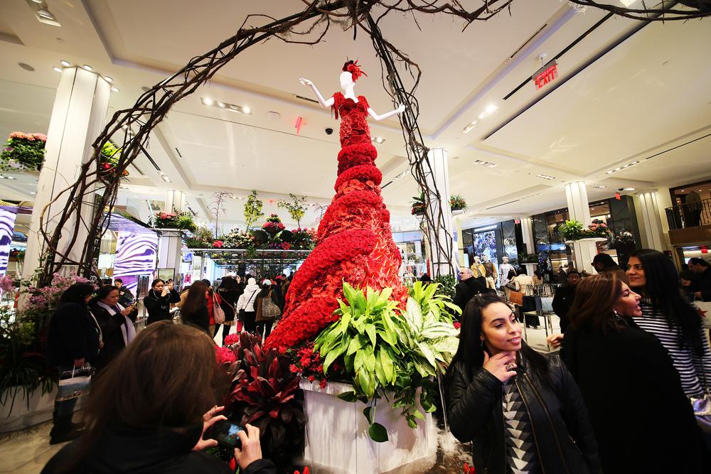 En cirka fyra meter hög kvinna i röd balklänning av rosor väntar i entrén.