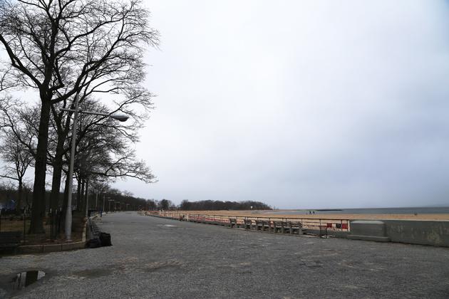 Stranden är formad som en halvmåne med ett stenlagt promenadstråk ovanför.