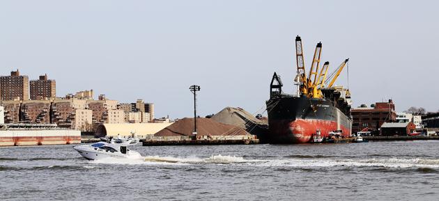 En (rätt ful, om du frågar mig) yacht passerar en grustanker som lastar eller lossar vid en pir i Brooklyn.