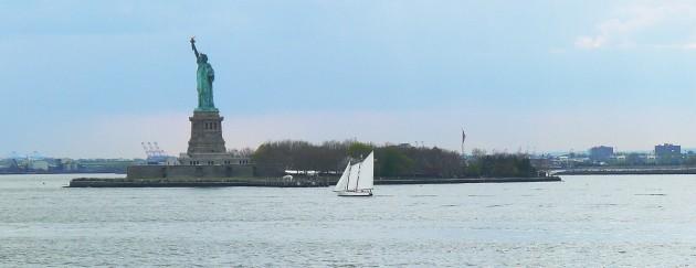 En segelbåt passerar Frihetsgudinnestatyn.